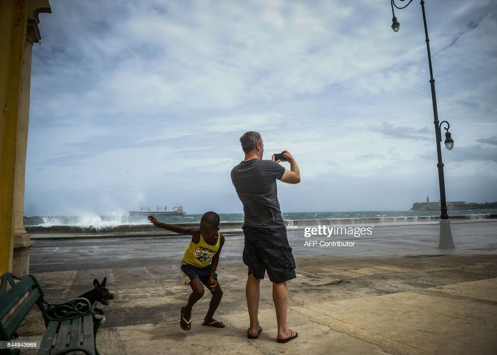 A tourist takes pictures of Havana's Malecon, on September 9, 2017. Irma's blast through the Cuban coastline weakened the storm to a Category Three, but it is still packing 125 mile-an-hour winds (205 kilometer per hour) and was expected to regain power before hitting the Florida Keys early Sunday, US forecasters said. The Cuban government extended its maximum state of alert to three additional provinces, including Havana, amid fears of flooding in low-lying areas. /