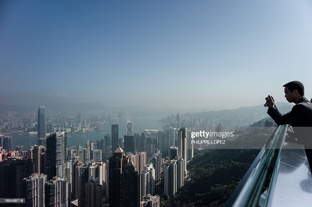 A tourist takes pictures of the city's skyline over a thin haze of pollution on a clear day in Hong Kong on February 1, 2013. Emissions from factories in southern China, which seep over Hong Kong's border, combined with local emissions from power plants and transport, generate an almost daily thick blanket of haze over the teeming metropolis. AFP PHOTO / Philippe Lopez