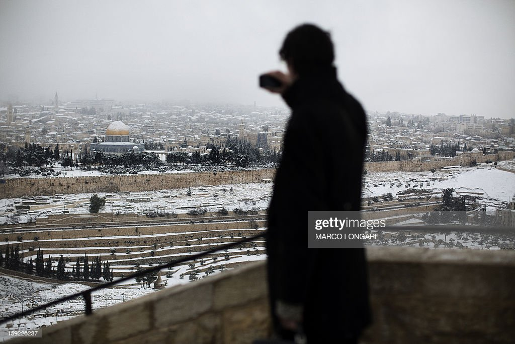 A tourist takes pictures of the snow-covered Al-Aqsa Mosque compound in the old city of Jerusalem on January 10, 2013. Jerusalem was transformed into a winter wonderland after heavy overnight snowfall turned the Holy City and much of the region white, bringing hordes of excited children onto the streets. AFP PHOTO/MARCO LONGARI