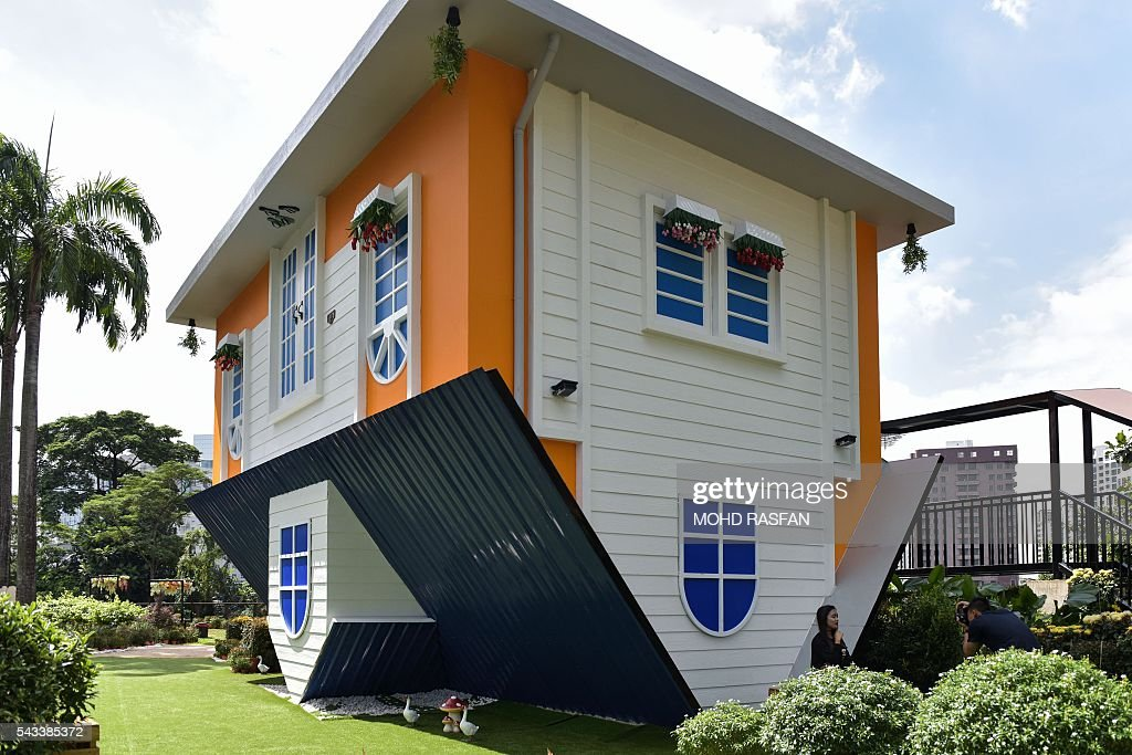 A tourist (R) takes pictures outside the Kuala Lumpur Upside Down House at KL Tower in Kuala Lumpur on June 28, 2016. Kuala Lumpur Upside Down House is a two-storey house and is the latest attraction for tourists arriving to the Malaysian capital where everything inside such as the furniture are placed in an upside down position. / AFP / MOHD