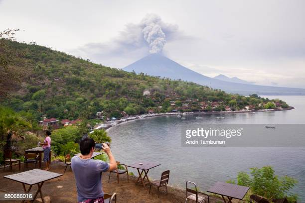 KARANGASEM BALI INDONESIA NOVEMBER 28 A tourist taking a photo of Mount Agung spewing volcanic ash from the popular Sunset Point in Amed on November...