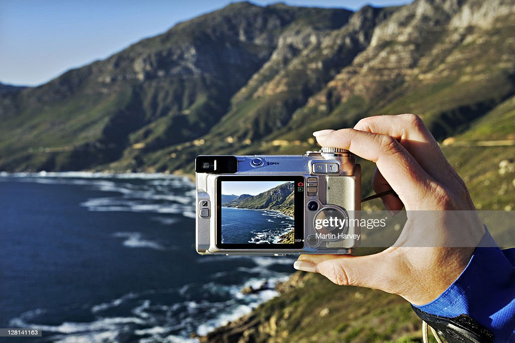 Tourist taking a picture of the view of Atlantic ocean from Chapmanís Peak drive. Western Cape Province, South Africa : Stock Photo