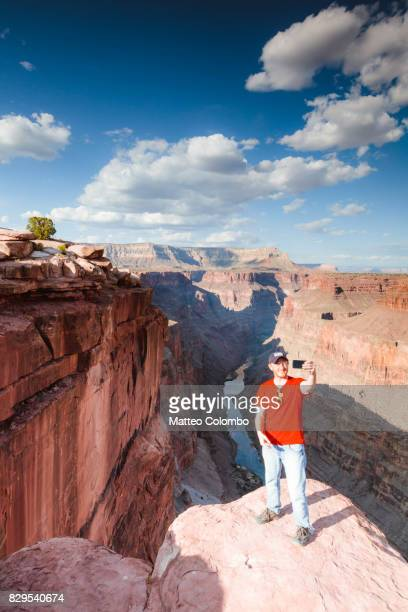 Tourist taking a selfie at overlook over Grand Canyon