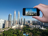 Tourist taking digital picture of Petronas Towers