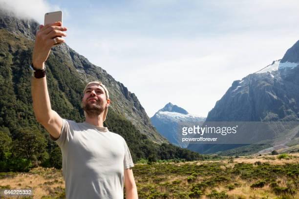 Tourist taking photo at Mount Talbot in Fiordland National Park, New Zealand
