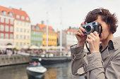 Tourist taking photos in Nyhavn, Copenhagen.