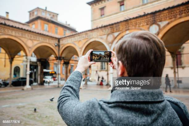 Tourist taking picture of porticos with his smartphone in Bologna, Italy