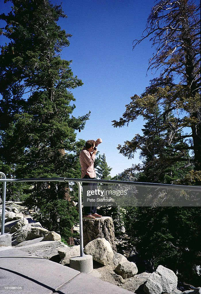 Tourist taking pictures of a landscape : Stock Photo