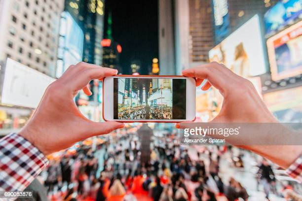 Tourist taking pictures of Times Square with his smart phone at night, personal perspective
