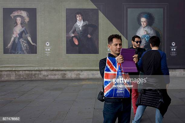 A tourist to Britain takes a photo with a modern handheld device near potraits by the Spanish romantic artist Francesco Goya sponsored by Credit...