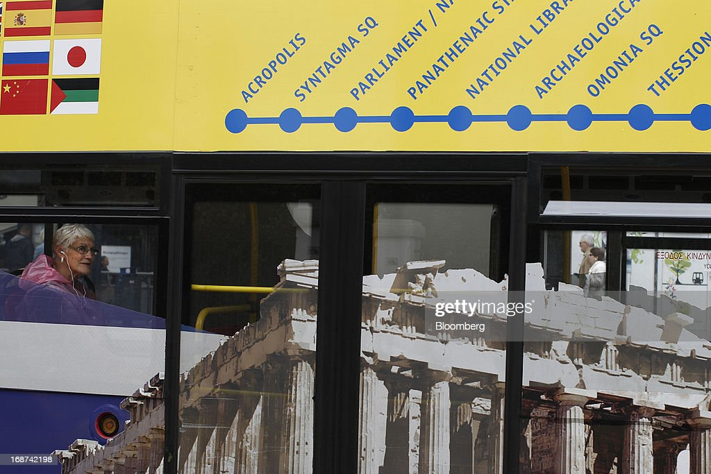 A tourist travels on a tourist bus decorated with a photograph of the Parthenon Temple through central Athens, Greece, on Tuesday, May 14, 2013. Greek Prime Minister Antonis Samaras said the country can beat the targets set under its 240 billion-euro ($311 billion) International Monetary Fund and euro area bailout program and return to bond markets in the first half of next year. Photographer: Kostas Tsironis/Bloomberg via Getty Images