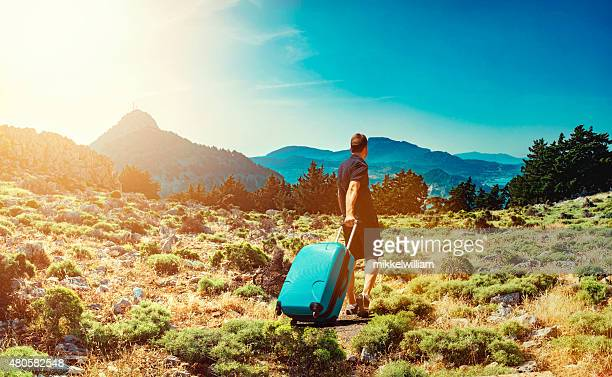 Tourist travels with suitcase thorugh the mountains on foot