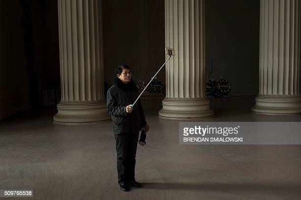 A tourist uses a selfie stick to take photos with a smart phone at the Lincoln Memorial February 12 2016 in Washington DC / AFP / Brendan Smialowski