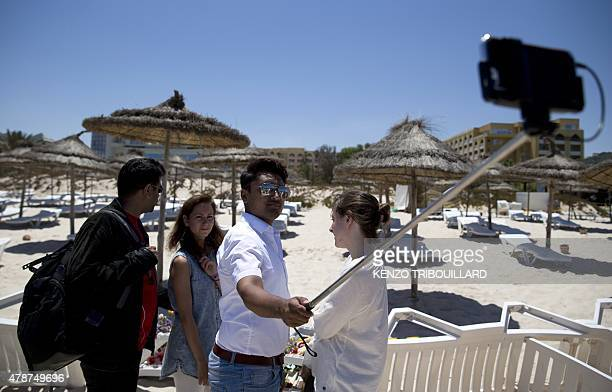A tourist uses a selfiestick to took a picture at the site of a shooting attack on the beach in front of the Riu Imperial Marhaba Hotel in Port el...