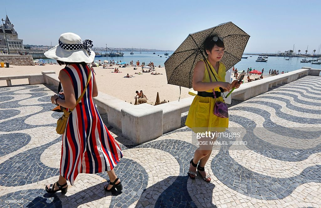 A tourist uses an umbrella to protect from the sun as she goes for a walk by Cascais' beach on the outskirts of Lisbon on June 29 2015 Temperatures...