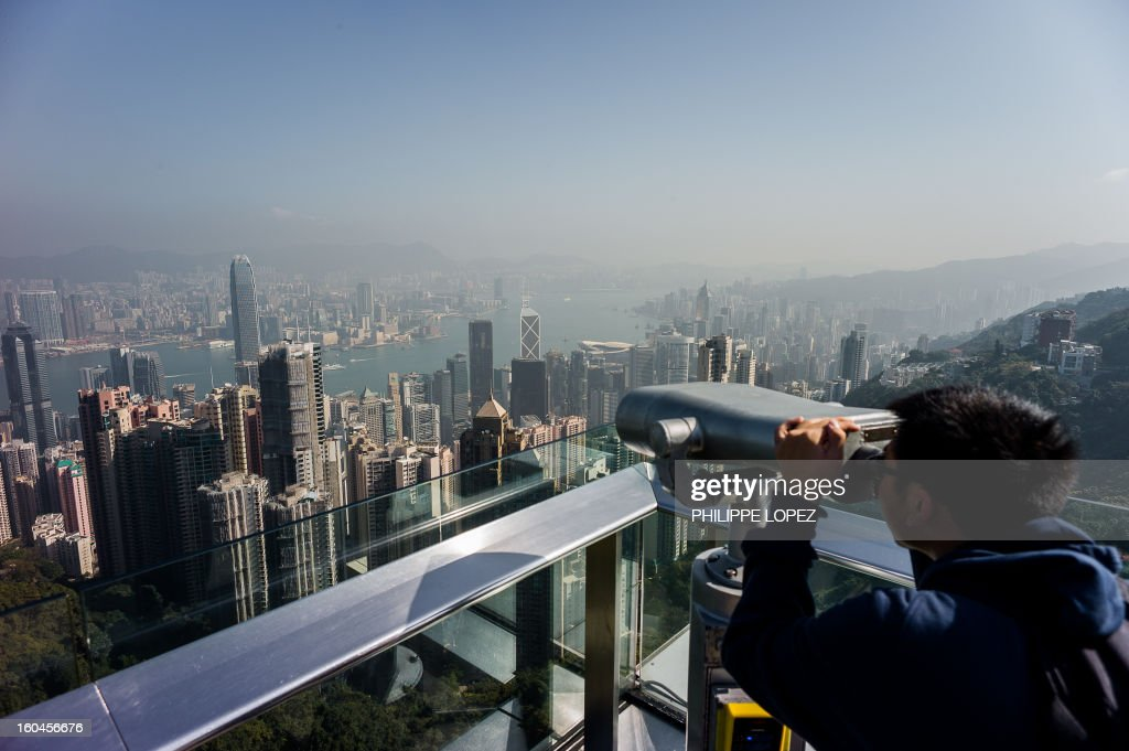 A tourist uses binoculars to view the city's skyline over a thin haze of pollution on a clear day in Hong Kong on February 1, 2013. Emissions from factories in southern China, which seep over Hong Kong's border, combined with local emissions from power plants and transport, generate an almost daily thick blanket of haze over the teeming metropolis. AFP PHOTO / Philippe Lopez