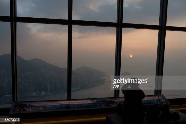 A tourist uses his camera to photograph the setting sun as he looks over Hong Kong's Victoria Harbour from an observation deck in Kowloon on November...
