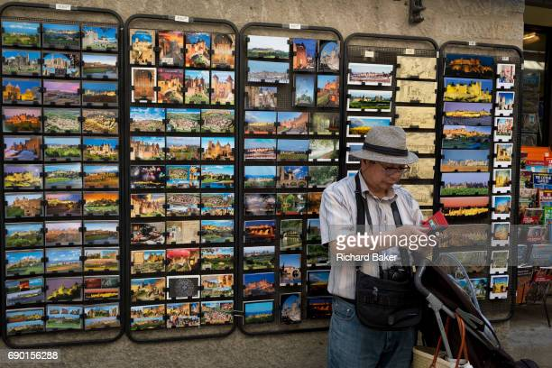 A tourist uses phone apps alongside a rack of postcards showing local scenes and historical ocations on 27th May in Carcasonne LanguedocRousillon...