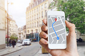Tourist using GPS map navigation app on smartphone screen to get direction to destination address in the city streets, travel and technology