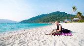 Tourist using laptop on the beach