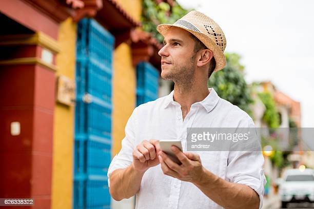 Tourist using map on his cell phone while sightseeing