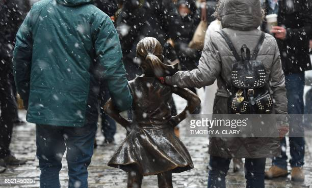 Tourist venture out to take photos of the ' Fearless Girl ' statue on Wall Street in New York March 10 2017 as snow hits the area and frigid...