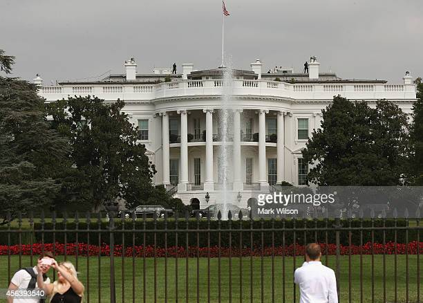 Tourist visit the south side of the White House as members of the US Secret Service stand guard on the roof September 30 2014 in Washington DC White...