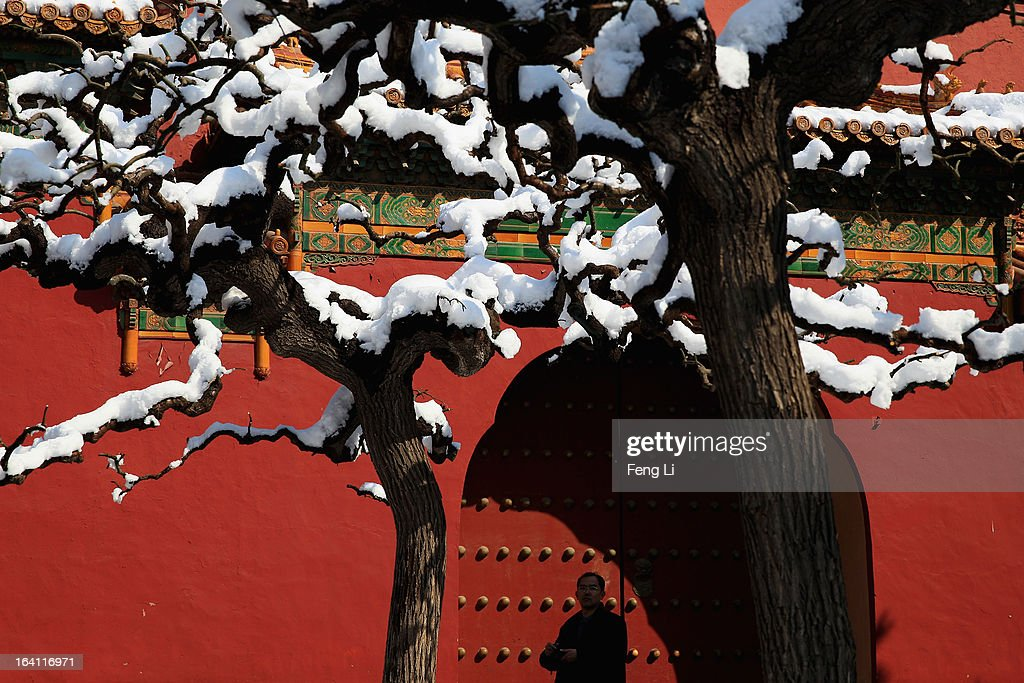 A tourist visits the Imperial Ancestral Temple following overnight snowfall on March 20, 2013 in Beijing, China. Beijing witnessed a heavy spring snowfall with a depth reaching 10-17 centimeters overnight.