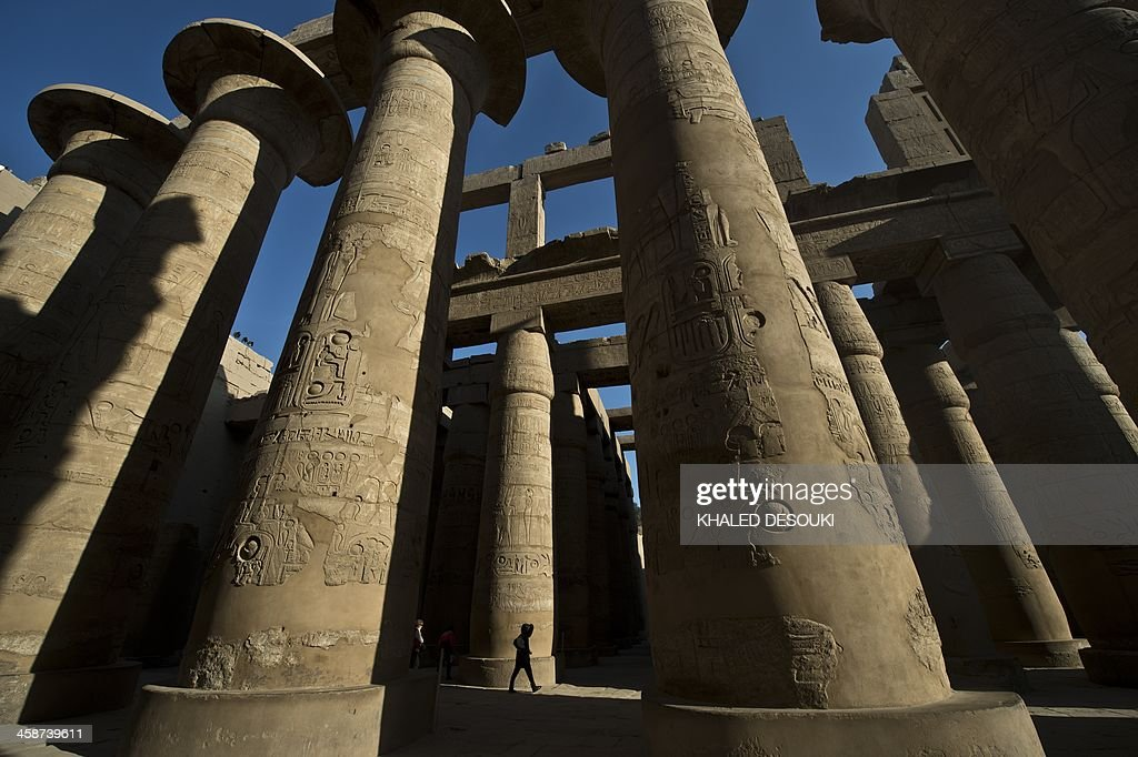 A tourist visits the Temple of Karnak to watch the winter solstice at sunrise in the southern Egyptian city of Luxor on December 21, 2013. The central sector of the site which takes up the largest amount of space, is dedicated to the Egyptian god Amun, who became prominent as the greatest of the gods. AFP PHOTO / KHALED DESOUKI