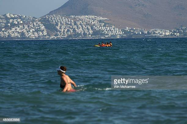 A tourist wades in shallow water as a boat full of migrants paddle their small boat near the beach after crossing a three mile stretch of the Aegean...
