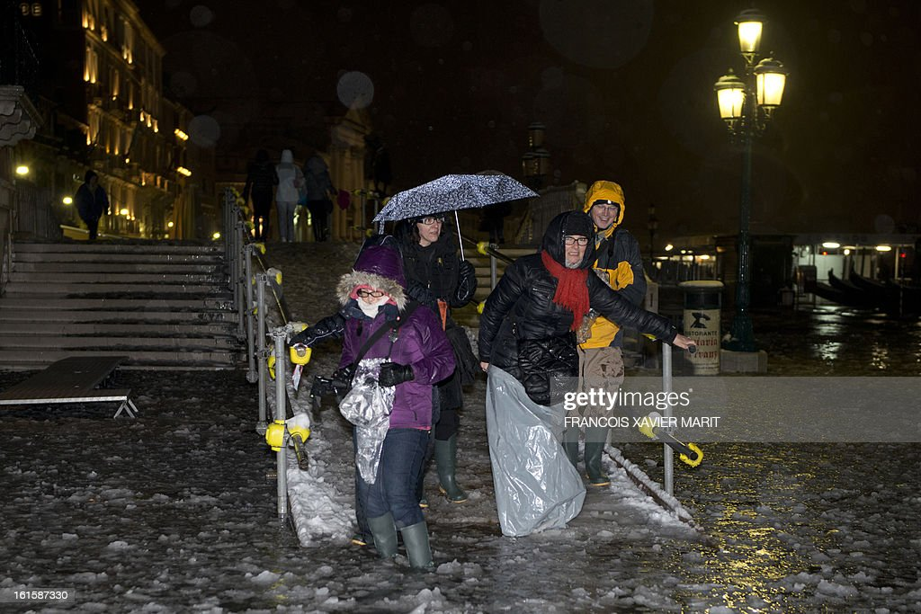 Tourist walk in the icy water during an acqua-alta (high-water) late on February 11, 2013 in Venice. The 'acqua alta', a convergence of high tides and a strong sirocco, reached 143 centimetres around midnight. AFP PHOTO / FRANCOIS XAVIER MARIT