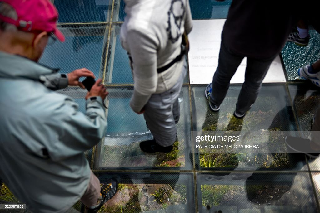 Tourist walk on a glass floor lookout on top of a cliff of Cabo Girao in Camara de Lobos, on Madeira island on April 30, 2016. An 81 years old French tourist died today after falling into a 100 meters deep ravine while he was trekking on the hills of Camara de Lobos, in the Portuguese island of Madeira, firefighters said. / AFP / PATRICIA