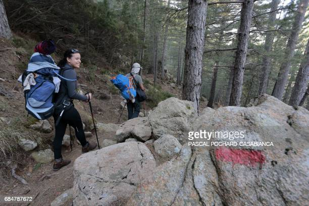Tourist walk on the GR 20 treck on April 4 2017 close to the Bavella picks in Zonza on the French Mediterranean island of Corsica / AFP PHOTO /...