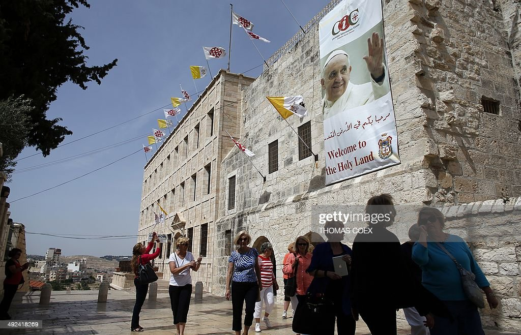 Tourist walk past a banner bearing a portrait of Pope Francis displayed on the wall of the Saint Catherine Church inside the Church of Nativity in the West Bank Town of Bethlehem, on May 20, 2014. Pope Francis will be treading on sensitive ground on an upcoming trip to the Middle East that is intended to promote inter-faith dialogue but has already sparked protests from ultra-orthodox Jews and radical Islamists.