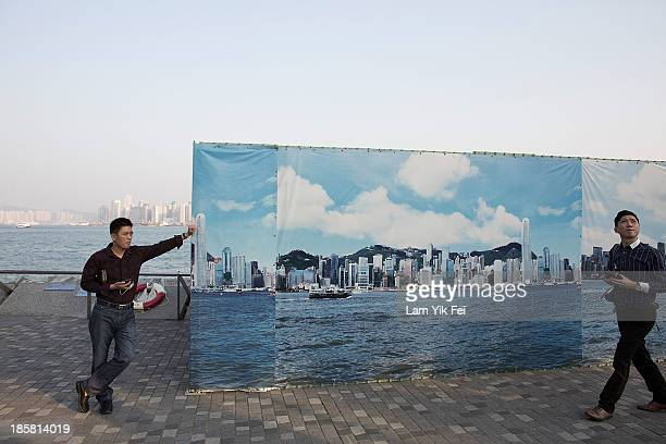 Tourist walk past a billboard featuring photos of the city skyline with a clear sky on October 25 2013 in Hong Kong A government warning has been...