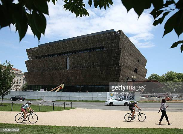 Tourist walk past the Smithsonian Museum of African American History and Culture that is currently under construction July 16 2015 in Washington DC...