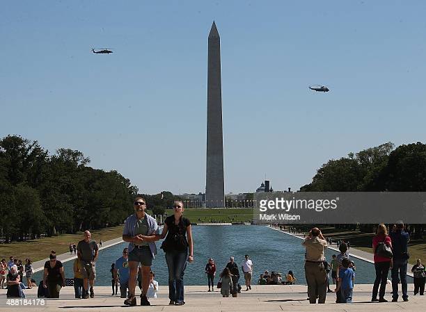 Tourist walk up to visit the Lincoln Memorial as Marine One carrying US President Barack Obama flies past the Washington Monument after taking off...