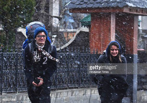 Tourist walking at the ridge during snowfall on January 14 2015 in Shimla India Shimla and its surrounding resorts of Kufri Fagu and Narkanda had...