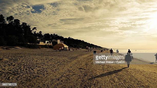 Tourist Walking On Beach Against Cloudy Sky