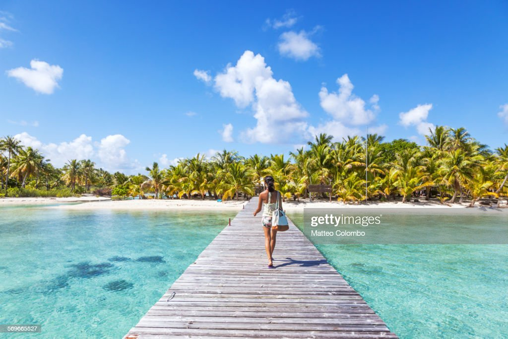 Tourist walking on jetty to tropical island : Stock Photo
