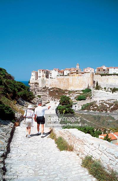 Tourist walking on the rock path, Bonifacio, Corsica, France