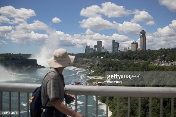 A tourist walks across the Niagara Falls International Rainbow Bridge in Niagara Falls Ontario Canada on Wednesday June 21 2017 The 150th anniversary...