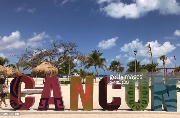 Tourist walks along the beach in Cancun Quintana Roo Mexico on March 28 2017 Cancun is the most recognized Mexican tourist center in the world and...
