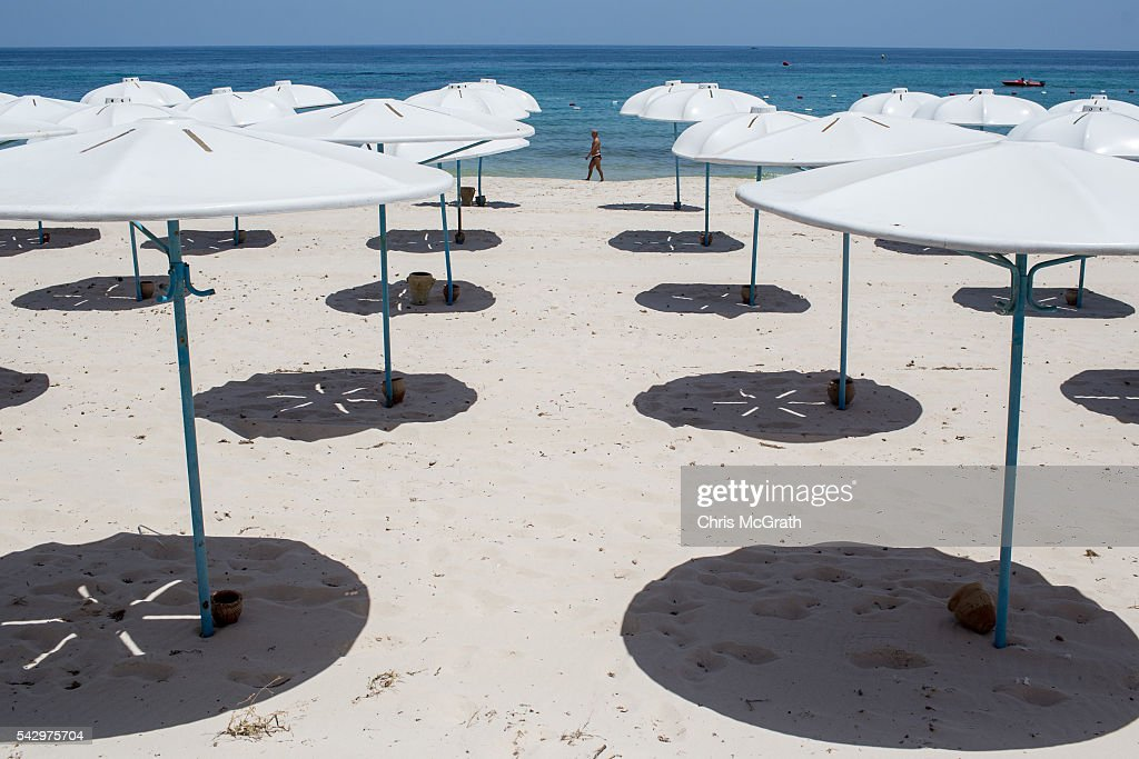 A tourist walks along the beach past an empty holiday resort on June 25, 2016 in Sousse, Tunisia. Before the 2011 revolution, tourism in Tunisia accounted for approximately 7% of the countries GDP. The two 2015 terrorist attacks at the Bardo Museum and Sousse Beach saw tourism numbers plummet even further forcing hotels to close and many tourism and hospitality workers to lose their jobs. The 26th of June marks the first anniversary of the Sousse beach attacks.