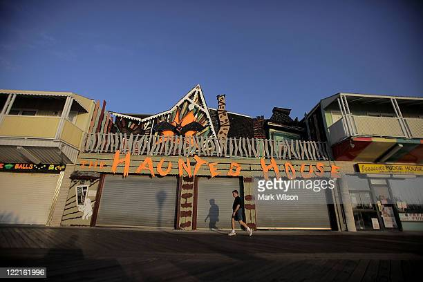 A tourist walks in front of the closed Haunted House on the usually crowded boardwalk on August 26 2011 in Ocean City Maryland Ocean City Mayor Rick...