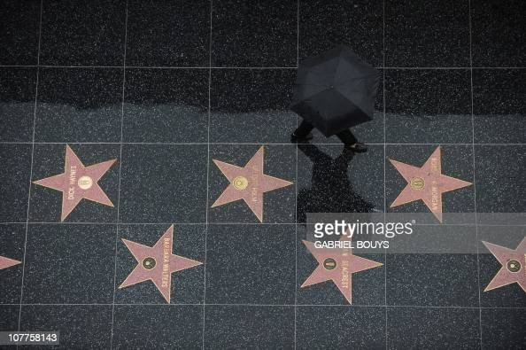 A tourist walks in the rain on the stars of the Hollywood Walk of Fame in Hollywood California on December 22 2010 Downtown Los Angeles received...