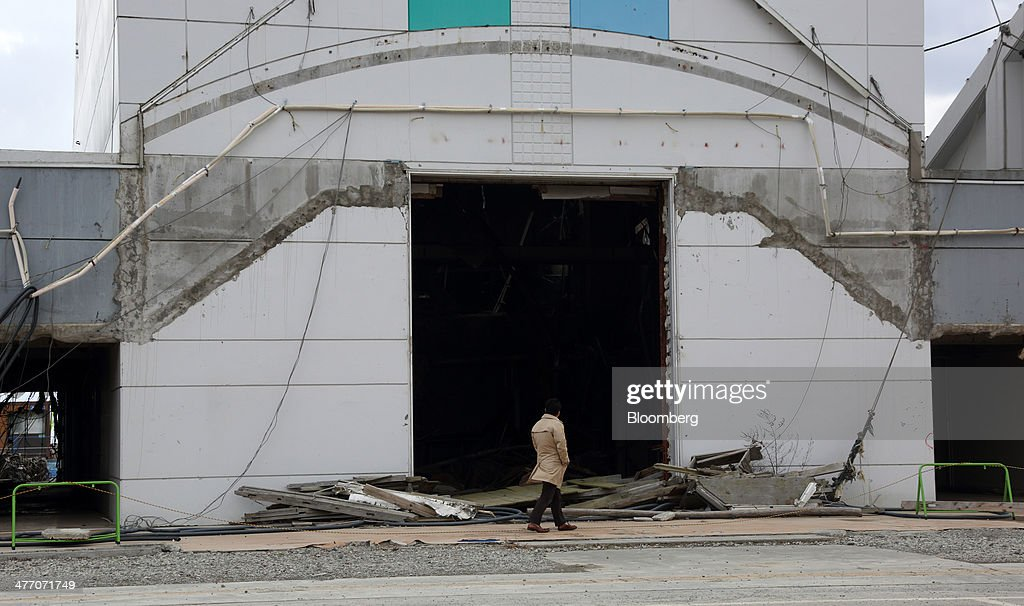 A tourist walks past a damaged building in Rikuzentakata, Iwate Prefecture, Japan, on Thursday, March 6, 2014. Reconstruction of Tohoku, the northern Japan region devastated by the 2011 tsunami, continues as the third anniversary of the disaster approaches. Photographer: Tomohiro Ohsumi/Bloomberg via Getty Images