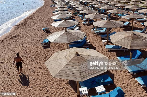 A tourist walks past sunbeds on a beach in Egypt's Red Sea resort of Sharm ElSheikh on November 10 2015 As visitors stranded after the crash of a...
