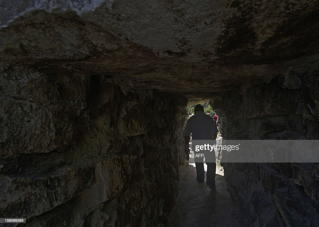 A tourist walks through the tunnel of the House of the Cenote at Tulum archaeological park, 130 km south of Cancun, Mexico on December 19, 2012. Mexico is one of five countries preparing to celebrate on December 21, the end of the Maya Long Count Calendar --Baktun 13-- which began in 3114 BC. AFP PHOTO/Pedro Pardo