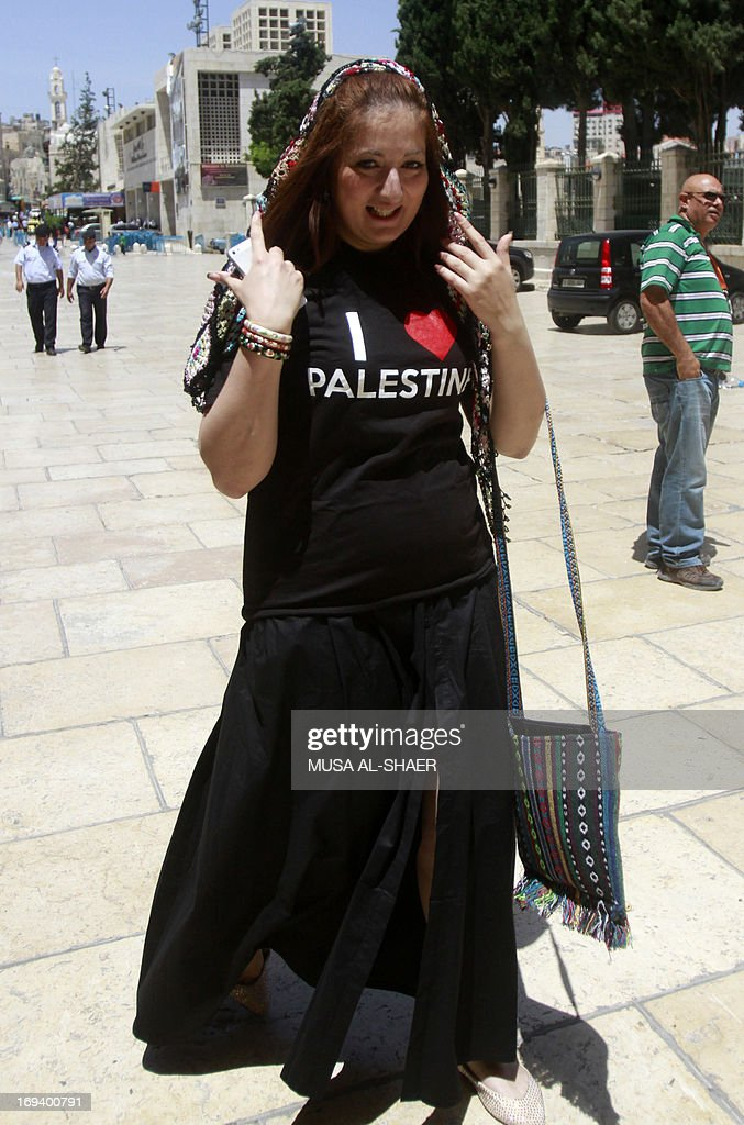 A tourist walks wearing a T-shirt reading 'I love Palestine' that she received from Palestinian youths as part of a campaign to raise awareness among foreign visitors about Palestinian indentity on May 24, 2013 in front of the Church of the Nativity in the West bank town of Bethlehem. AFP PHOTO/MUSA AL SHAER